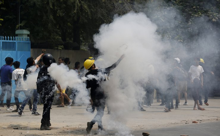 Demostrators hurl back tear gas canisters towards police during a protest against the military coup Saturday, March 27, 2021, in Mandalay, Myanmar. AP