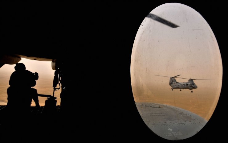 In this file photo a US soldier (L) sits in the rear of a Marine Chinook helicopter while flying over Camp Bastion in Helmand province, southwest of Kabul on May 3, 2008. AFP