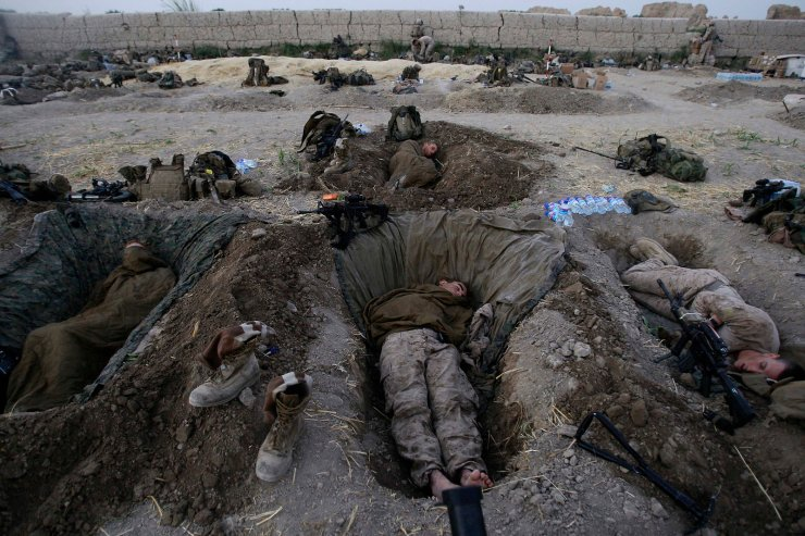 U.S. Marines from the 2nd MEB, 1st Battalion 5th Marines sleep in their fighting holes inside a compound where they stayed for the night, in the Nawa district of Afghanistan's Helmand province, on July 8, 2009. AP