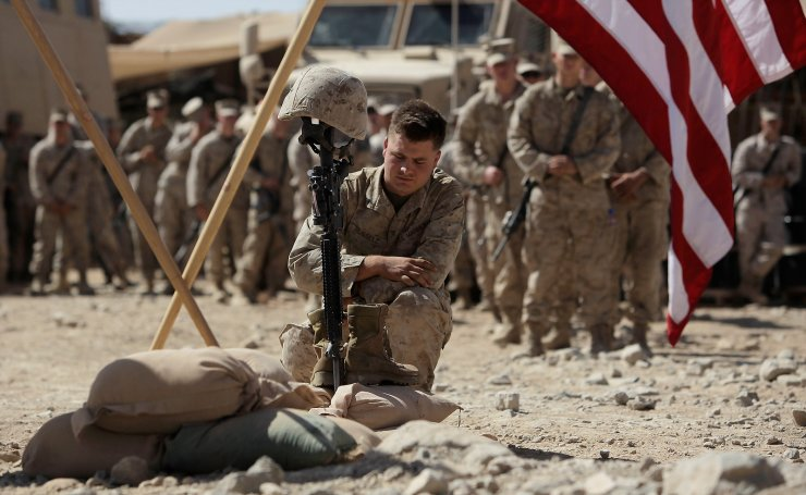 U.S. Marine Cpl. Russell pays his respects to Lance Cpl. Joshua Bernard during a memorial service at a forward operating base with Golf Company, 2nd Battalion, 3rd Regiment, 2nd MEB, 3rd MEF, Thursday, Aug. 27, 2009, in Now Zad in the Helmand Province of Afghanistan. Bernard was killed during a Taliban ambush on Aug. 14. AP
