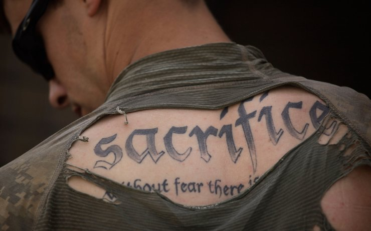 A tattoo on the back of U.S. Army Sgt. James Wilkes of Rochester, N.Y., is seen through his torn shirt after a foot patrol with 1st Platoon, Charlie Company, 2nd Battalion, 1st Infantry Regiment, of the 5th Styker Brigade on May 8, 2010, in Afghanistan's Kandahar province. AP