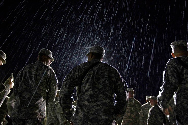 1st Lt. Nikesh Kapadia, 24, center, of Queens, N.Y., with the U.S. Army's 4th Brigade Combat Team, 101st Airborne Division out of Fort Campbell, Ky., stands in the rain while waiting to go through customs at the Transit Center in Manas, Kyrgyzstan, on the way home after completing a deployment in Afghanistan on Aug. 10, 2011. AP