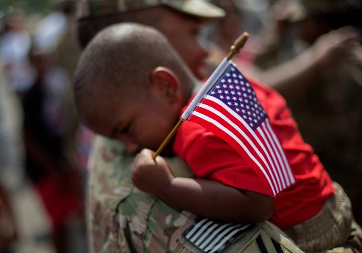 Tyson Hicks, 2, holds an American flag while in the arms of his father, Sgt. 1st Class Gabriel Hicks, who had just returned from a deployment to Afghanistan with the Georgia National Guard's 48th Infantry Brigade Combat Team on Sept. 16, 2014, in Macon, Ga. AP