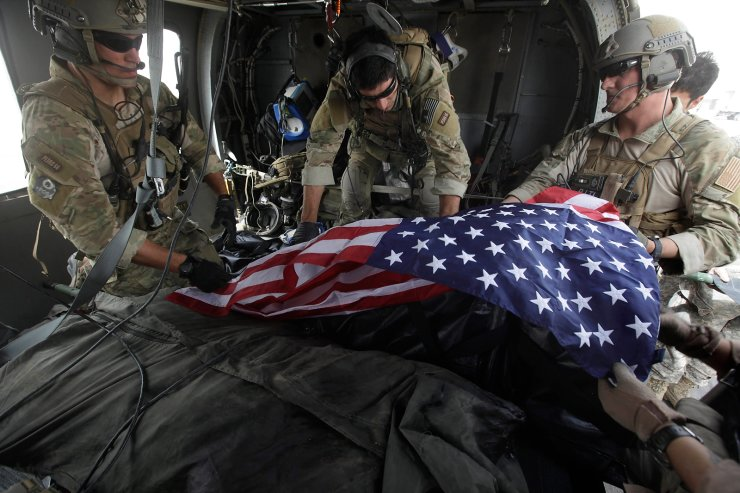 Upon landing after a helicopter rescue mission, Tech. Sgt. Jeff Hedglin, right, an Air Force Pararescueman, or PJ, drapes an American flag over the remains of the first of two U.S. soldiers killed minutes earlier in an IED attack, assisted by fellow PJs, Senior Airman Robert Dieguez, center, and 1st Lt. Matthew Carlisle, in Kandahar province, southern Afghanistan on July 29, 2010. AP