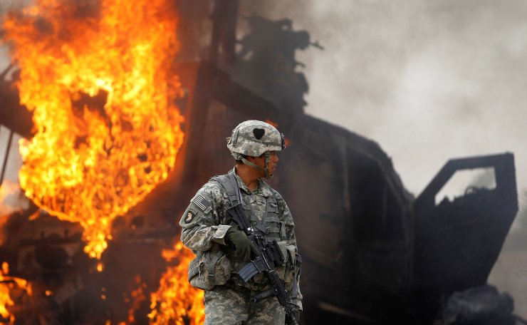 Captain Melvin Cabebe with the US Army's 1-320 Field Artillery Regiment, 101st Airborne Division stands near a burning M-ATV armored vehicle after it struck an improvised explosive device (IED) near Combat Outpost Nolen in the Arghandab Valley north of Kandahar, Afghanistan, July 23, 2010.  REUTERS