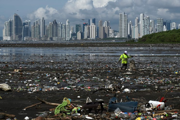 A man collects garbage, including plastic waste, at the beach of Costa del Este, in Panama City, on April 19, 2021. AFP