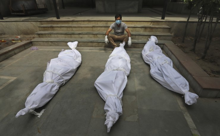 A man waits for the cremation of a relative who died of COVID-19, placed near bodies of other victims, in New Delhi, India, Tuesday, April 20, 2021. AP