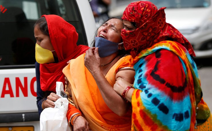 A woman is consoled after her husband died due to the coronavirus disease (COVID-19) outside the mortuary of a COVID-19 hospital in Ahmedabad, India, April 20, 2021. REUTERS