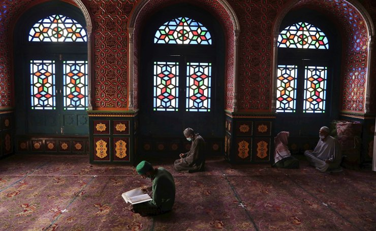 A Kashmiri Muslim man recites the Koran, the holy book of Muslims, as others pray during the holy month of Ramadan at a shrine in Srinagar, the summer capital of Indian Kashmir, 21 April 2021. EPA