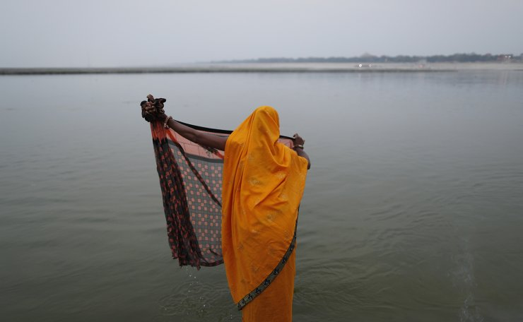 A Hindu devotee washes her cloth after performing an evening ritual at Sangam, the confluence of the rivers Ganges and Yamuna on Ram Navami in Prayagraj, India, Wednesday, April 21, 2021. AP