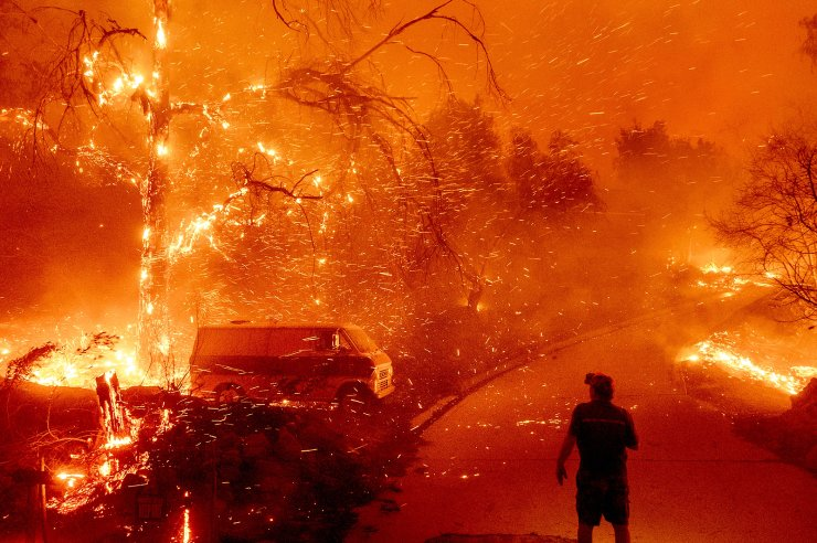 Bruce McDougal watches embers fly over his property as the Bond Fire burns through the Silverado community in Orange County, Calif. As the impact of climate change becomes more apparent, misinformation about it is shifting to focus more and more on extreme weather. AP