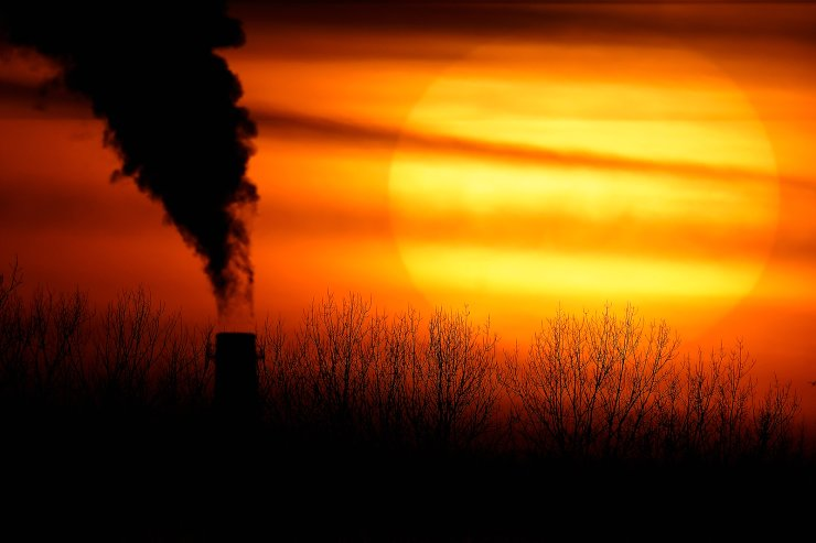 In this Feb. 1, 2021 file photo, emissions from a coal-fired power plant are silhouetted against the setting sun in Independence, Mo. President Joe Biden is convening a coalition of the willing, the unwilling, the desperate-for-help and the avid-for-money for a two-day summit aimed at rallying the world's worst polluters to do more to slow climate change. Biden's first task when his virtual summit opens Thursday is to convince the world that the United States is both willing and able isn't just willing to meet an ambitious new emissions-cutting pledge, but also able. AP