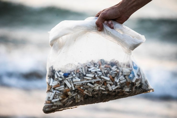 Julian Melcer holds a plastic bag filled with cigarette butts he collected from the shore of the Mediterranean Sea as part of his environmental campaign, at a beach in Tel Aviv, Israel April 20, 2021. Picture taken April 20, 2021. REUTERS