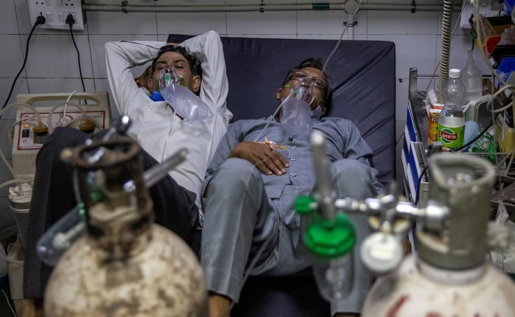 Patients suffering from COVID-19 share a bed as they receive treatment at the casualty ward in Lok Nayak Jai Prakash (LNJP) hospital in New Delhi, India April 15, 2021. REUTERS