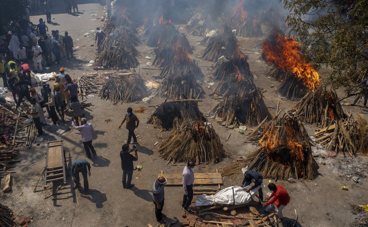 Multiple funeral pyres of victims of COVID-19 burn at a ground that has been converted into a crematorium for mass cremation in New Delhi, India, Saturday, April 24, 2021. Indian authorities are scrambling to get medical oxygen to hospitals where COVID-19 patients are suffocating from low supplies. AP