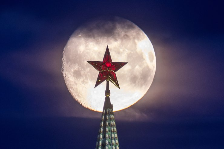 A star atop the Vodovzvodnaya Tower of the Moscow Kremlin is seen against a full moon.TASS