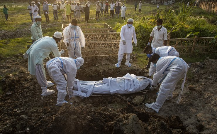 Municipal workers prepare to bury the body of a person who died of COVID-19 in Gauhati, India, Sunday, April 25, 2021. AP