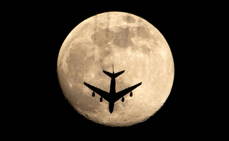 An aeroplane is pictured against an almost full moon, in Iraq's southern city of Basra, on April 25, 2021. AFP