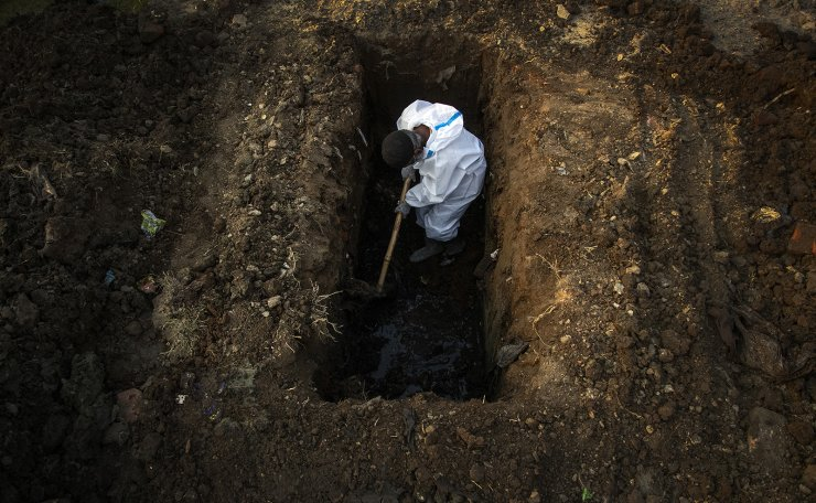 A man in protective suit digs earth to bury the body of a person who died of COVID-19 in Gauhati, India, Sunday, April 25, 2021. AP