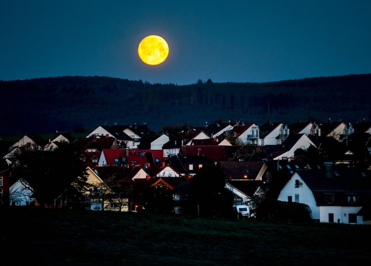 The moon sets over the small village of Obernhain near Frankfurt, Germany, Monday, April 26, 2021. AP