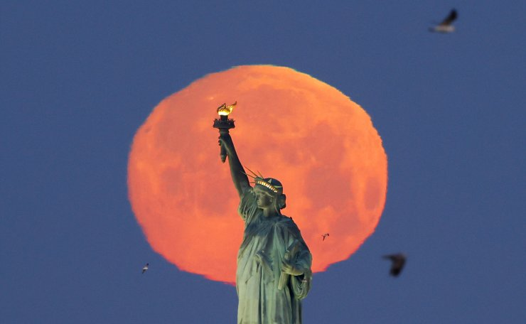 A Pink Supermoon sets behind the Statue of Liberty in New York City on Monday, April 26, 2021. This week's supermoon is dubbed the 'pink' moon because of its timing close to flower blooming season. UPI