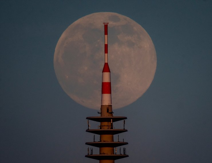 The full moon rises behind the television tower in Frankfurt, Germany, Monday, April 26, 2021. AP