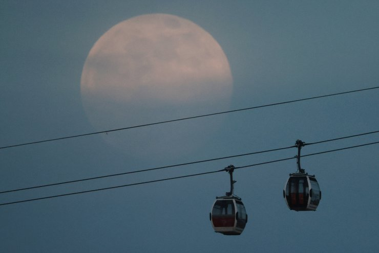 The full moon, also known as the Supermoon, rises above the Emirates Air Line cable car in London, Britain, April 26, 2021. REUTERS
