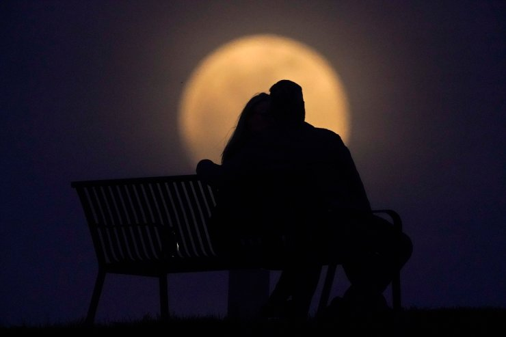 A couple watch the moon rise from from a park, Monday, April 26, 2021, in New Albany, Ind. This moon is a supermoon, meaning it appears larger than an average full moon because it is nearer the closest point of its orbit to Earth. AP