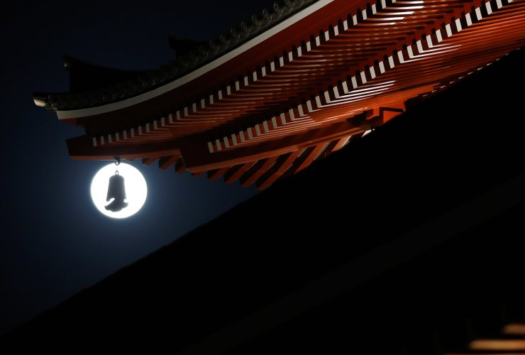 The full moon, also known as the Supermoon, is seen through a five-storied pagoda at Sensoji temple, in Tokyo, Japan April 27, 2021. REUTERS