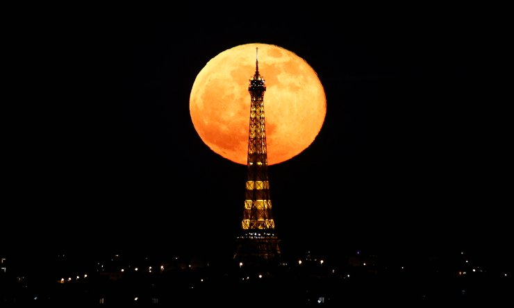 The full moon, known as the 'Super Pink Moon' rises behind the Eiffel Tower during a nationwide curfew due to tighter measures against the spread of the coronavirus disease (COVID-19) in Paris, France, April 27, 2021.  REUTERS