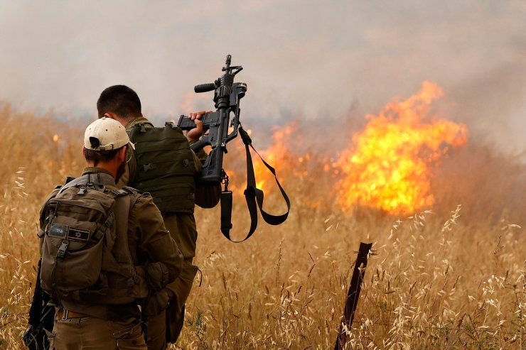 Israeli soldiers stand across a fire caused by incendiary balloons launched from the Gaza Strip, in a field near the southern Israeli kibbutz of Nir Am on May 9, 2021. AFP