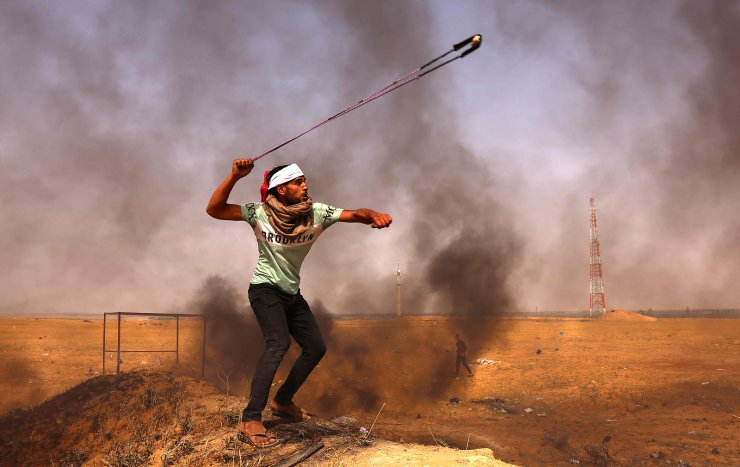 A Palestinian demonstrator hurls rocks with a slingshot next to burning tyres during a protest by the border with Israel, east of Rafah in the southern Gaza Strip, on May 10, 2021. AFP