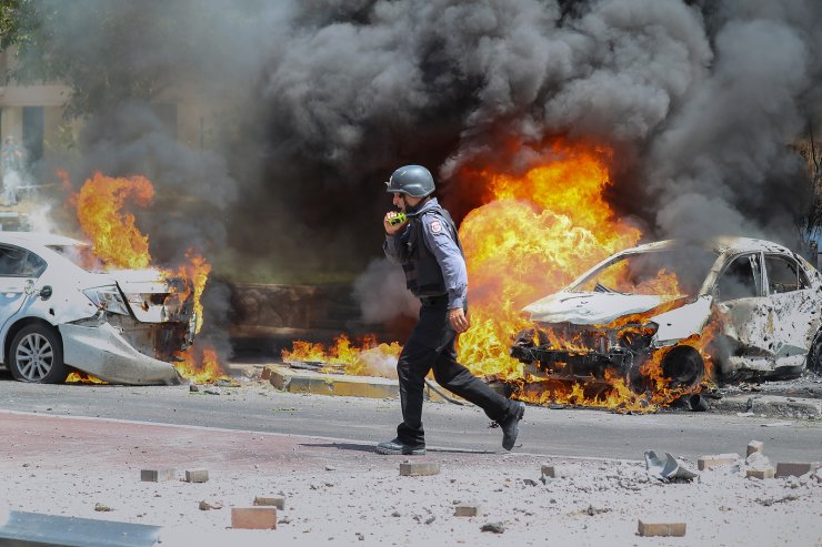 An Israeli firefighter walks next to cars hit by a missile fired from Gaza Strip, in the southern Israeli town of Ashkelon, Tuesday, May 11, 2021. AP