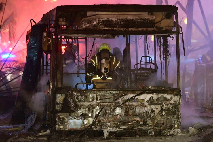 An Israeli firefighter extinguishes a burning bus after it was hit by a rocket fired from the Gaza Strip, at the central Israeli town of Holon, near Tel Aviv, Tuesday, May 11, 2021. AP