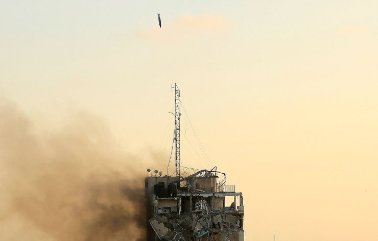 An air guided bomb can be seen hitting Al-Sharouk tower as it collapses during an Israeli air strike, in Gaza City on May 12, 2021. - An Israeli air strike destroyed a multi-storey building in Gaza City today, AFP reporters said, as the Jewish state continued its heavy bombardment of the Palestinian enclave. AFP