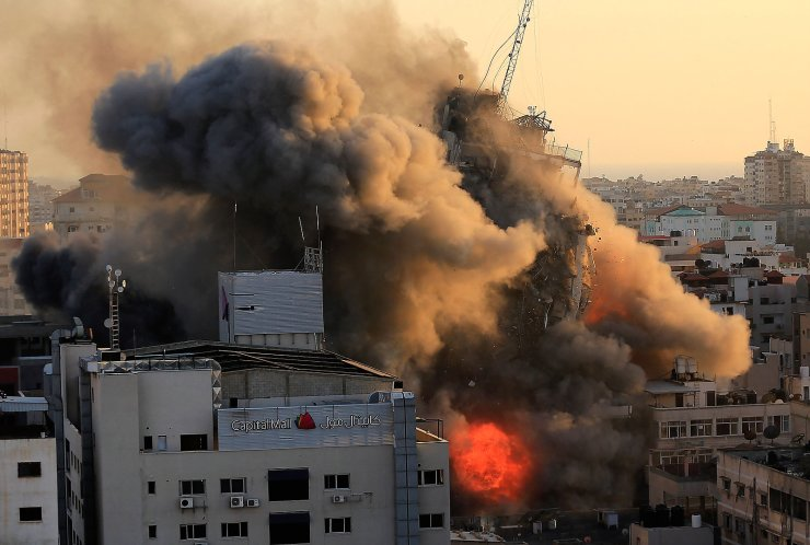 Heavy smoke and fire surround Al-Sharouk tower as it collapses during an Israeli air strike, in Gaza City on May 12, 2021. - An Israeli air strike destroyed a multi-storey building in Gaza City today, AFP reporters said, as the Jewish state continued its heavy bombardment of the Palestinian enclave. AFP