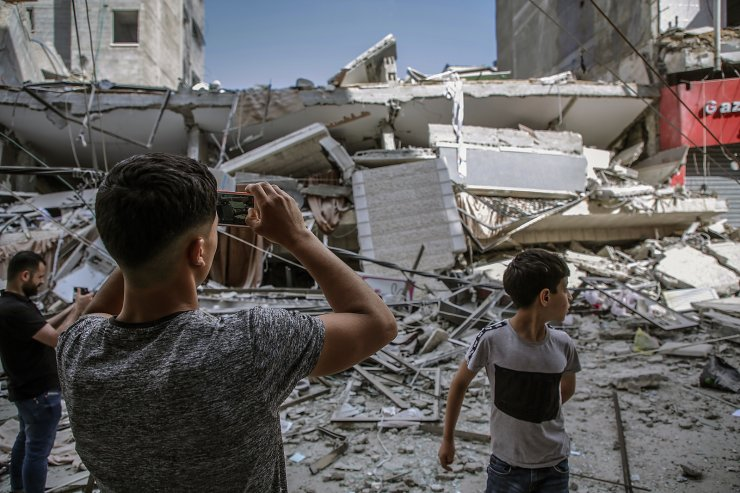 Palestinians inspect a destroyed house of Al-Turk family after an Israeli airstrike on Gaza Strip, 13 May 2021. EPA