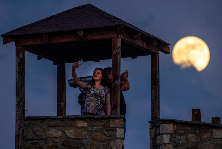A couple takes a selfie with the full moon in the background, the second and last super moon this year, called the 'Flower Moon,' as it rises over the castle in Skopje, Republic of North Macedonia, 25 May 2021. EPA