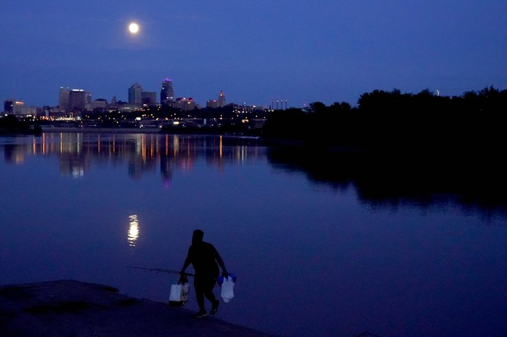 A man leaves after fishing in the Missouri River as the nearly full moon rises beyond the downtown skyline, late Tuesday, May 25, 2021, in Kansas City, Mo. AP
