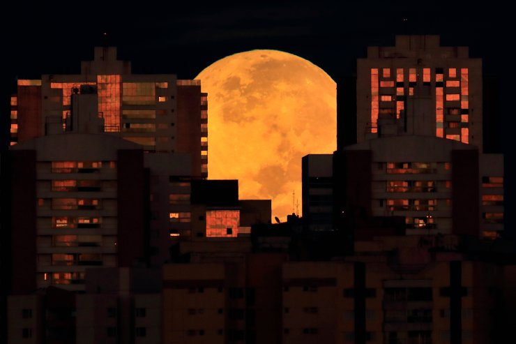 A lunar eclipse is observed during dawn in Brasilia, Brazil, Wednesday, May 26, 2021.  Wednesday's eclipse is the first in more than two years and coincides with a supermoon. AP