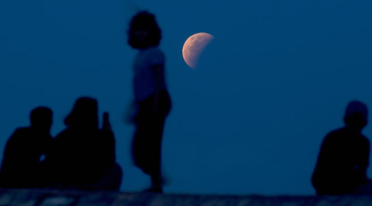 Residents watch the lunar eclipse at Sanur beach in Bali, Indonesia on Wednesday, May 26, 2021. The total lunar eclipse, also known as a super blood moon, is the first in two years with the reddish-orange color the result of all the sunrises and sunsets in Earth's atmosphere projected onto the surface of the eclipsed moon. AP