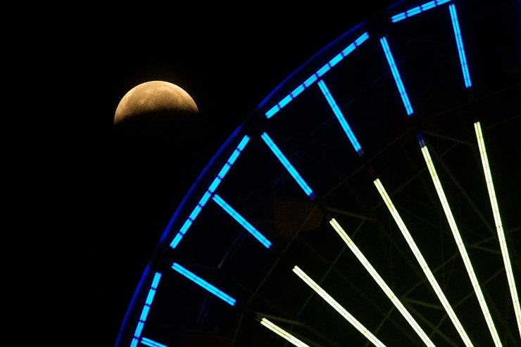 The lunar eclipse progresses is seen behind a ferris wheel over Santa Monica Beach in Santa Monica, Calif., Wednesday, May 26, 2021. The first total lunar eclipse in more than two years is coinciding with a supermoon for quite a cosmic show. AP