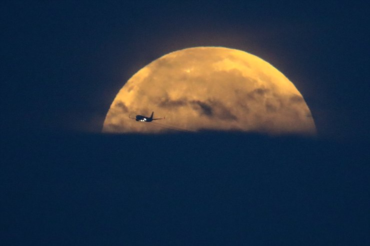 An airplane flies past as the full-moon sets over Santa Monica Beach in Santa Monica, Calif., Wednesday, May 26, 2021. The first total lunar eclipse in more than two years is coinciding with a supermoon for quite a cosmic show. AP