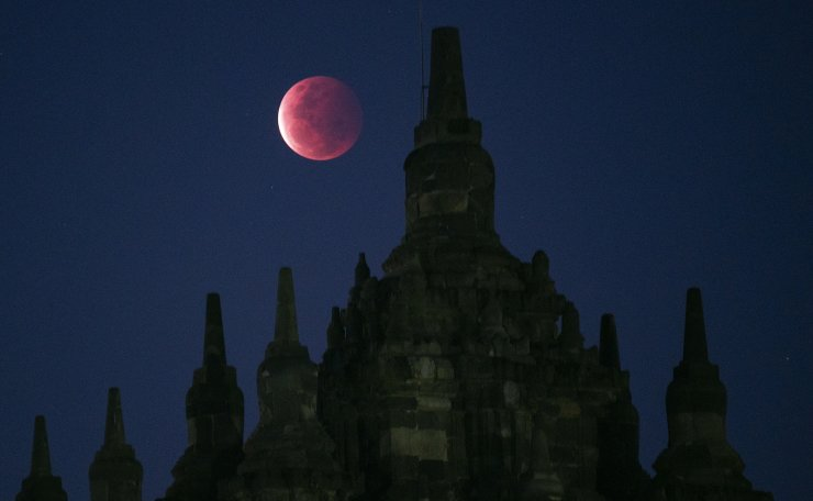 A full moon rises over the 9th century Plaosan Temple as a lunar eclipse was taking place in Yogyakarta, Indonesia, Wednesday, May 26, 2021. The first total lunar eclipse in more than two years coincides with a supermoon this week for quite a cosmic show. AP