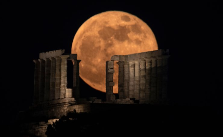 The flower supermoon rises behind the columns of the ancient marble temple of Poseidon at Cape Sounion, about 70 Km (45 miles) south of Athens, on Wednesday, May 26, 2021. AP