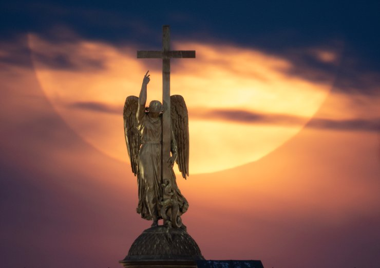 The full moon rises in the clouds over a statue of an angel fixed atop the Alexander Column at the Palace Square in St. Petersburg, Russia, Wednesday, May 26, 2021. AP