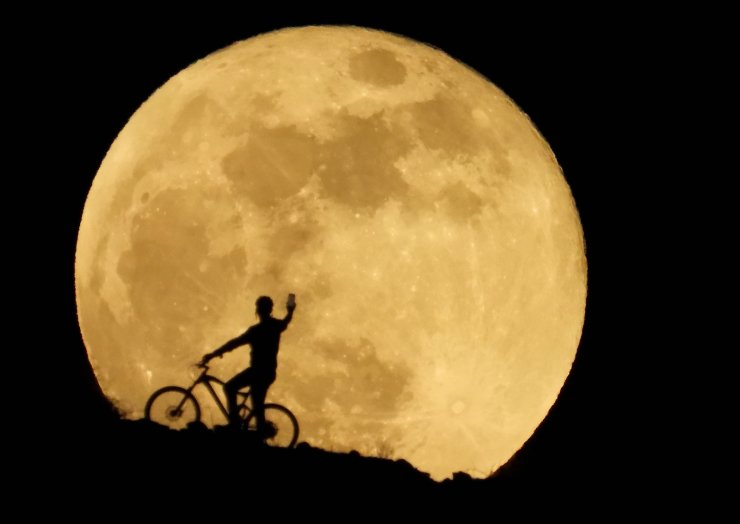 A cyclist uses a cellphone to photograph the full moon, known as the 'Super Flower Moon' as it rises over Arguineguin, in the south of Gran Canaria, Spain May 26, 2021. REUTERS