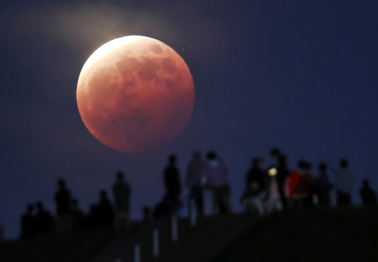 People watch the total eclipse of the moon at Moerenuma Park in Sapporo, northern Japan, 26 May 2021, as the super moon is passing through the shadow of the earth.  EPA
