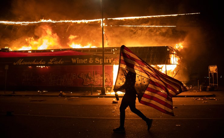 A protester carries a U.S. flag upside down, a sign of distress, next to a burning building, May 28, 2020, in Minneapolis. Protests over the death of George Floyd, a black man who died in police custody, broke out in Minneapolis for a third straight night. The image was part of a series of photographs by The Associated Press that won the 2021 Pulitzer Prize for breaking news photography. AP