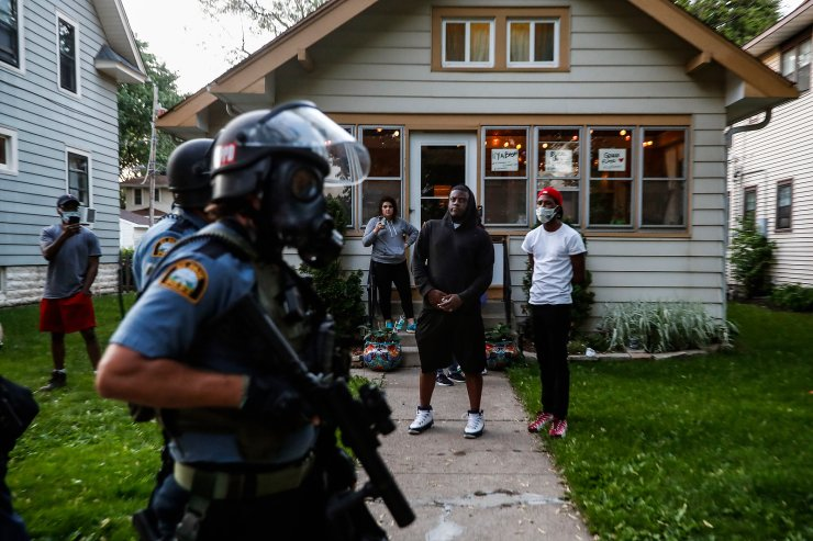 Bystanders watch as police walk down a street May 28, 2020, in St. Paul, Minn. Protests over the death of George Floyd, a black man who died in police custody, broke out in Minneapolis for a third straight night. The image was part of a series of photographs by The Associated Press that won the 2021 Pulitzer Prize for breaking news photography. AP